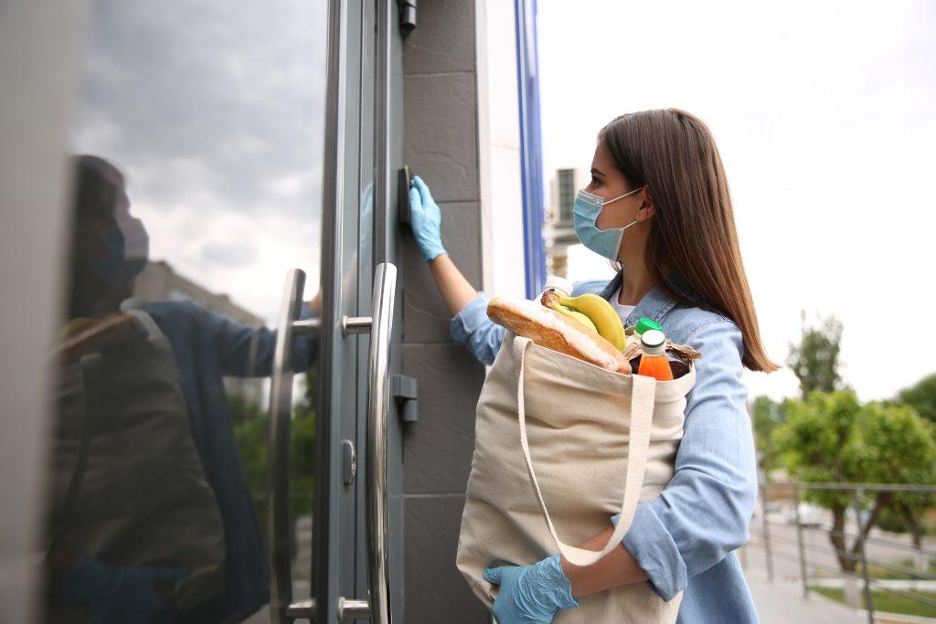 Femme bénévole avec des produits sonne à l'extérieur.